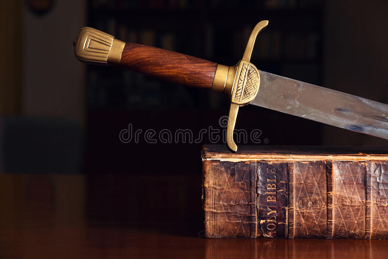 Espada en la biblia vieja imagen de archivo