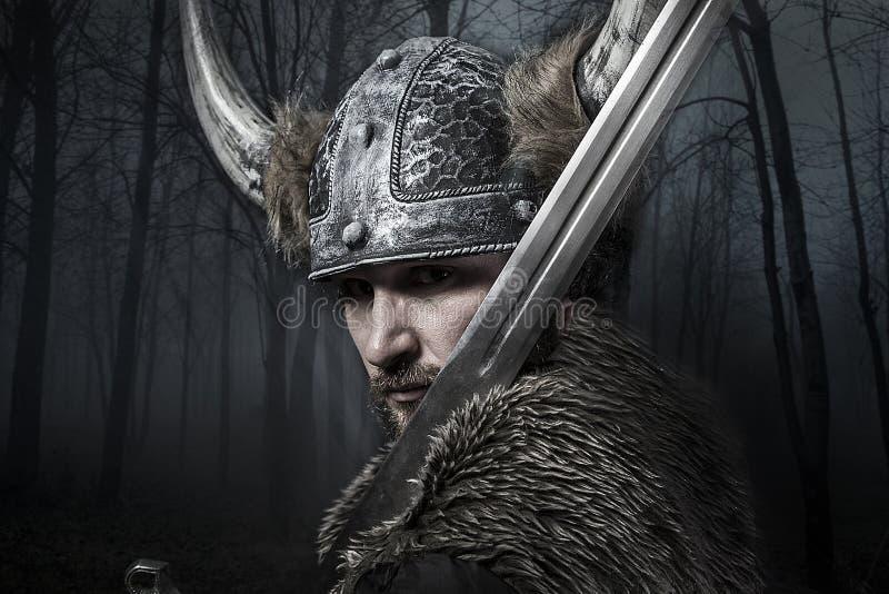 Espada, guerrero de Viking con el casco sobre fondo del bosque fotografía de archivo