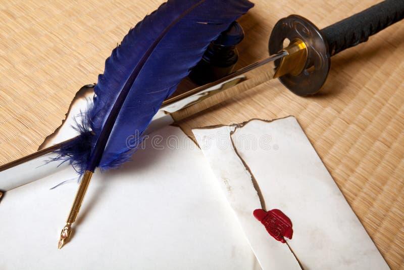 Espada y carta de la pluma imagen de archivo libre de regalías