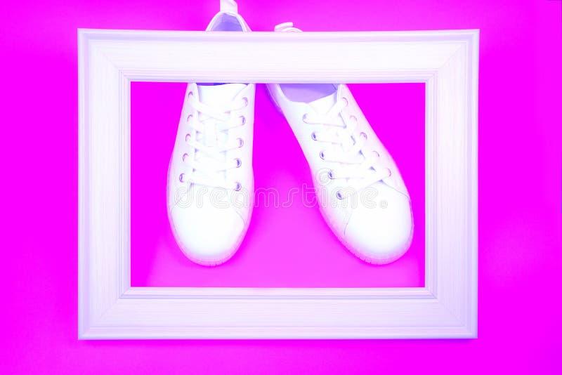 Espadrilles blanches et cadre en bois sur le fond rose au néon image stock