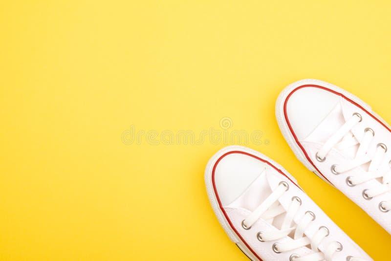 Espadrilles blanches sur le fond jaune image stock