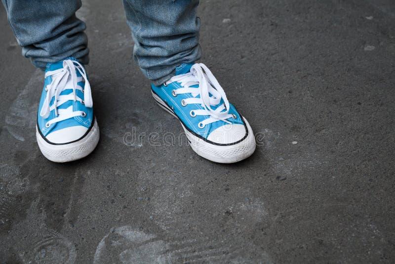 Espadrilles bleues, pieds d'adolescent dans des chaussures en caoutchouc photo libre de droits