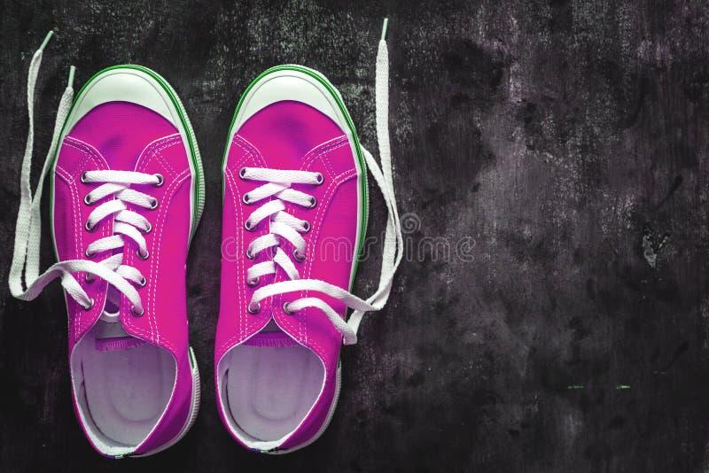 espadrilles de Pourpre-rose-lilas avec les dentelles déliées sur un fond concret foncé Copiez l'espace Vue de ci-avant images stock