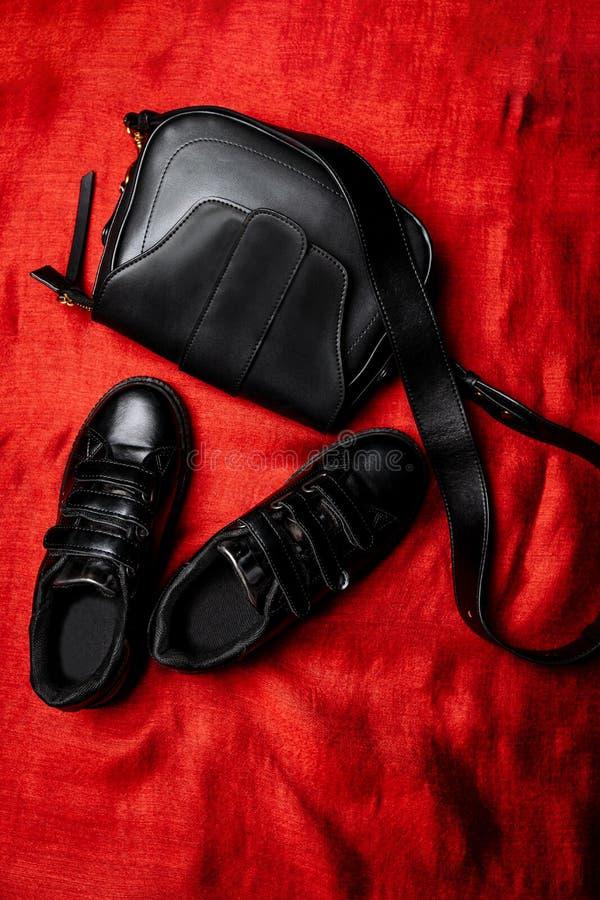 Espadrilles en cuir noires de Velcro et sac en cuir noir avec un aileron au-dessus du fond tissé images stock