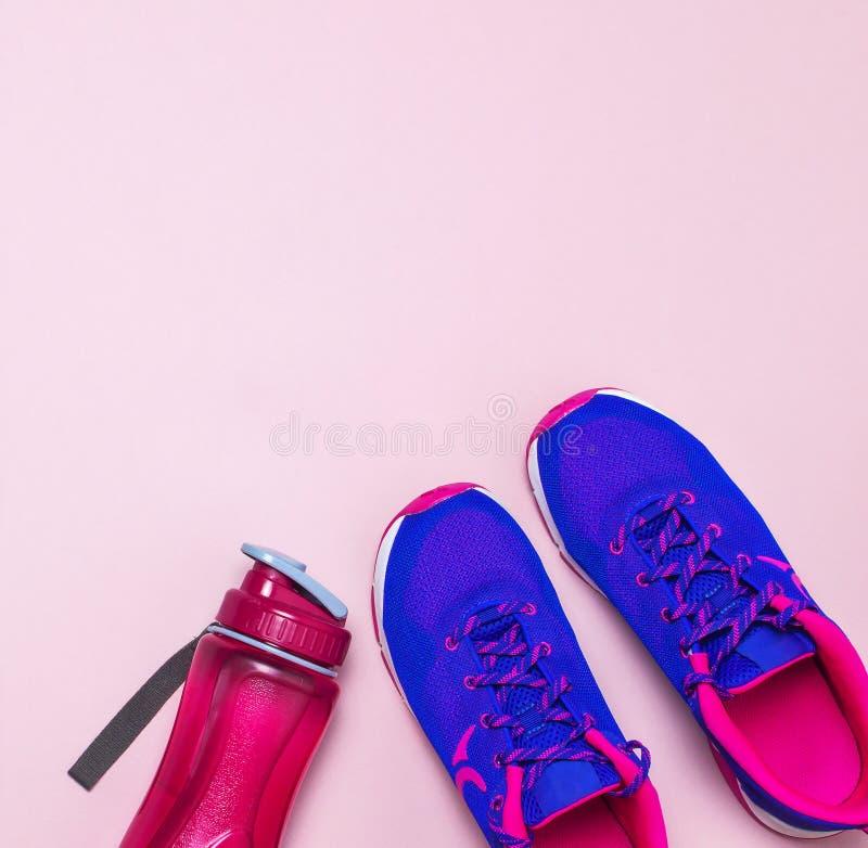 Espadrilles et bouteille d'eau femelles roses violettes ultra bleues sur la vue supérieure étendue par appartement rose en pastel photos stock