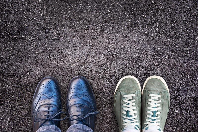 Espadrilles et chaussures d'affaires côte à côte sur l'asphalte, équilibre de la vie de travail photographie stock libre de droits