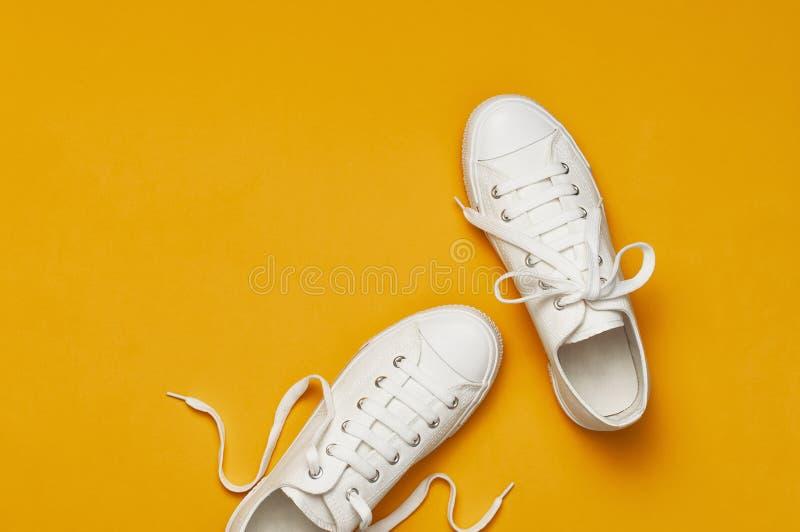 Espadrilles femelles blanches de mode sur le fond jaune-orange L'espace plat de copie de vue sup?rieure de configuration Chaussur images stock