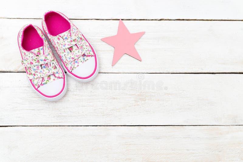 Espadrilles roses du ` s d'enfants et une étoile rose sur un fond en bois photographie stock libre de droits