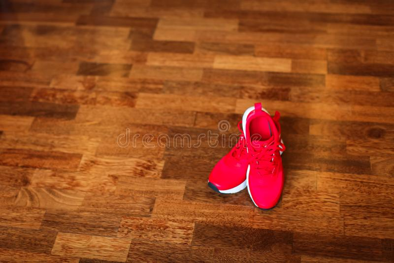Espadrilles rouges de gymnase de la jeunesse fraîche sur le plancher en bois de parquet brun avec l'endroit de copie images libres de droits