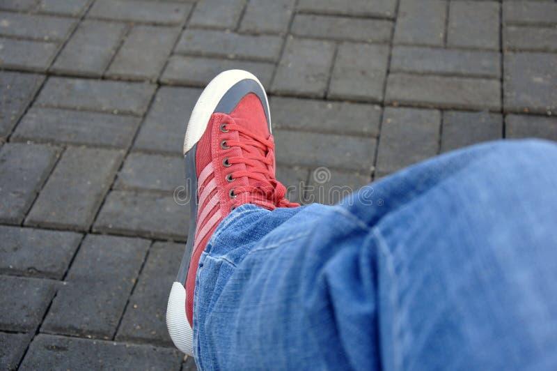Espadrilles rouges, jambes d'un jeune homme image stock