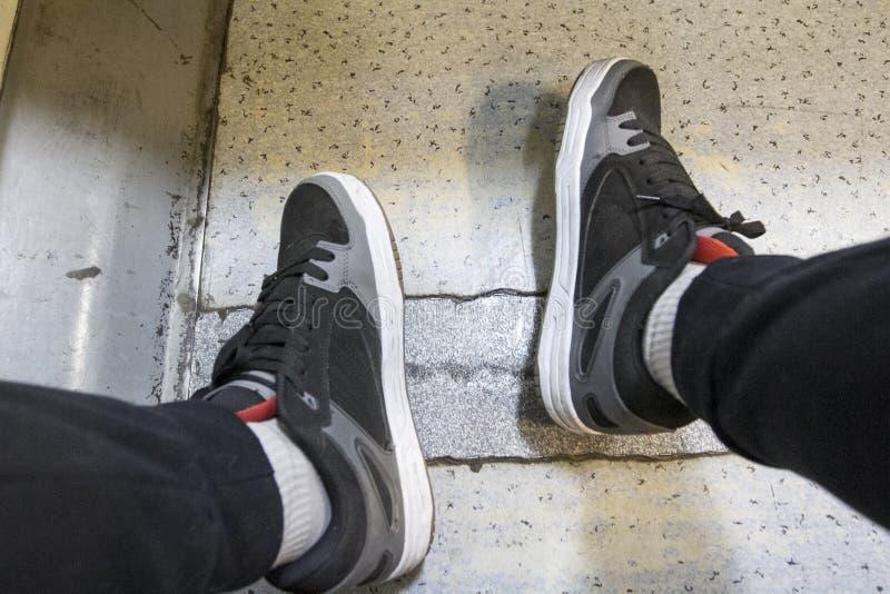 Espadrilles sur les jambes étroitement dans un train électrique photos libres de droits