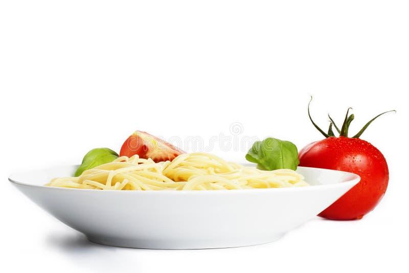 Espaguete em uma placa com tomate e manjericão foto de stock