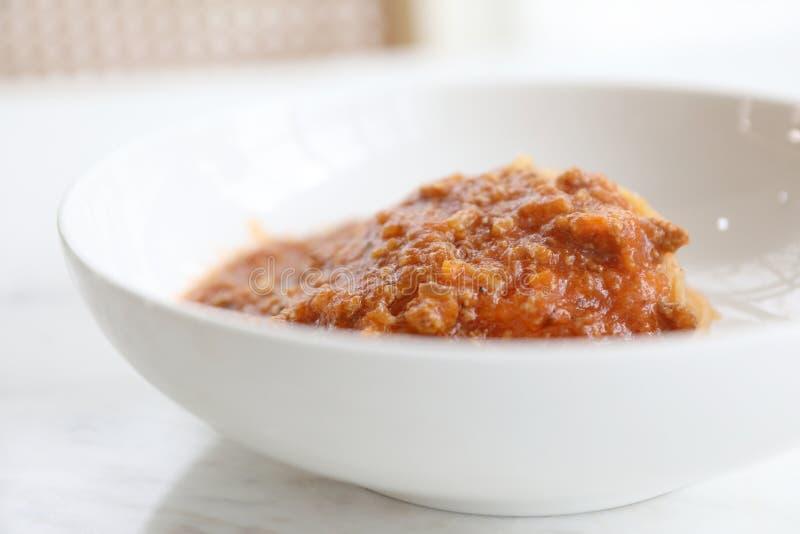 Espaguetes Bolonhês com o molho triturado da carne e de tomate decorado com queijo parmesão e manjericão, alimento italiano imagens de stock