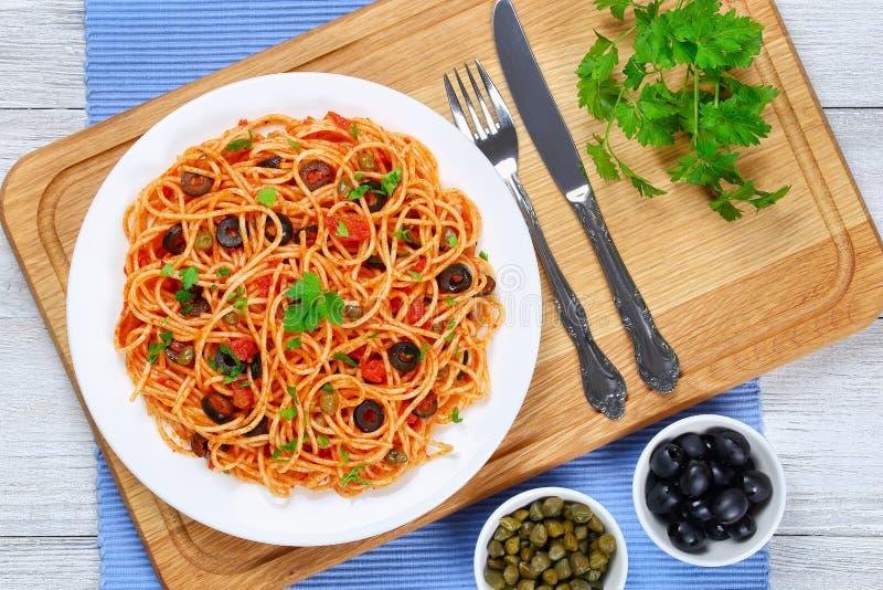 Espaguetes com alcaparras azeitonas, anchovas, molho de tomate fotografia de stock royalty free