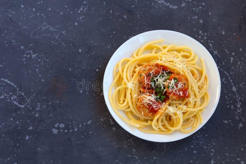 Espaguetes com almôndegas, molho de tomate e queijo parmesão na placa branca no fundo escuro foto de stock royalty free