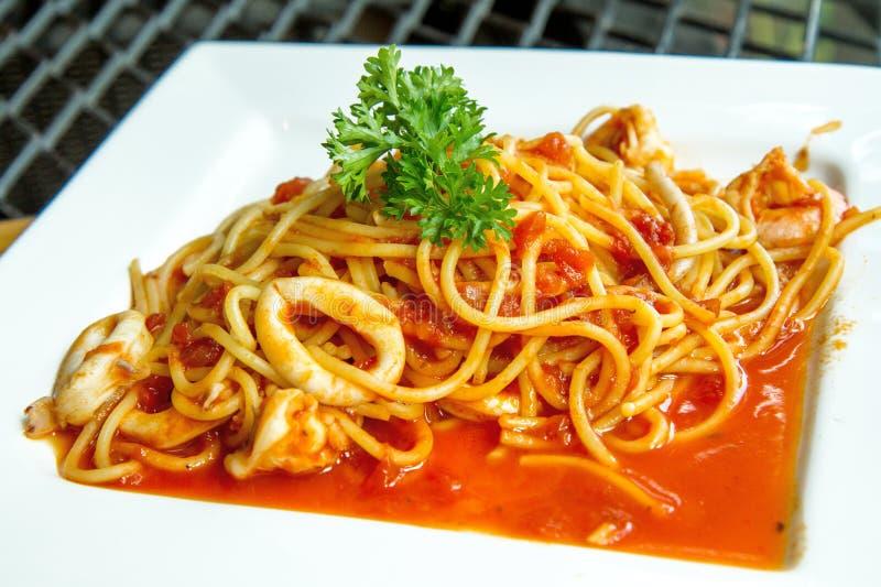 Espaguetes com calamar, camarões e molho de tomate foto de stock