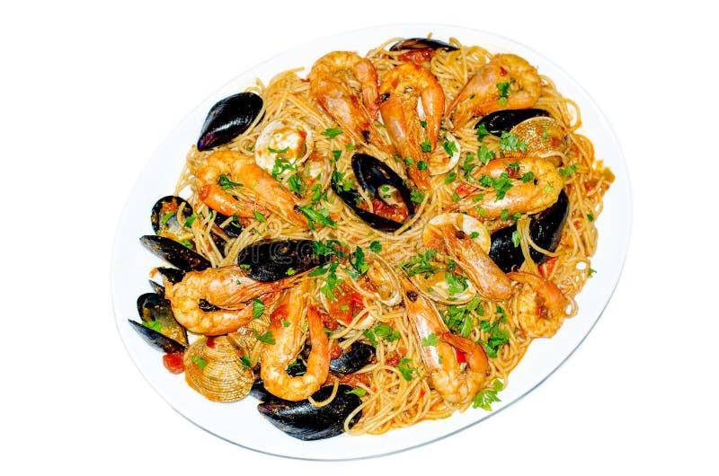 Espaguetes com camarões e mexilhões na placa isolada no branco M imagens de stock royalty free