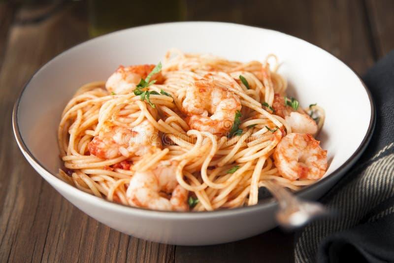 Espaguetes com camarões, molho de tomate e salsa desbastada fotografia de stock