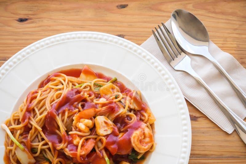 Espaguetes com molho e camarão vermelhos na placa branca sobre t de madeira imagens de stock royalty free