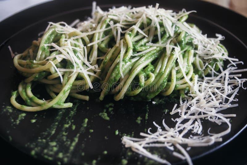 Espaguetes com molho verde da rúcula do alho e do azeite, com o queijo raspado colocado em um arco foto de stock royalty free