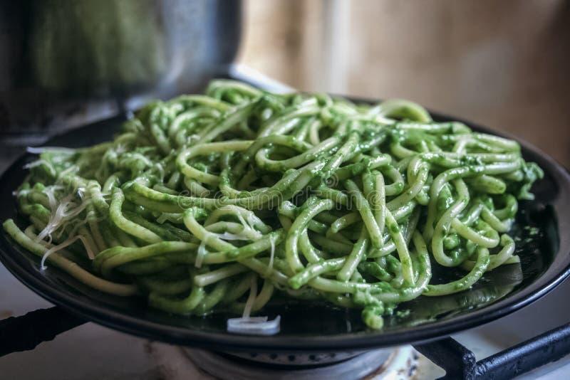 Espaguetes com molho verde da rúcula do alho e do azeite, com queijo derretido raspado foto de stock royalty free