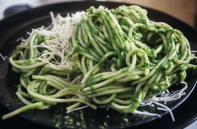 Espaguetes com molho verde da rúcula do alho e do azeite, com queijo raspado imagem de stock