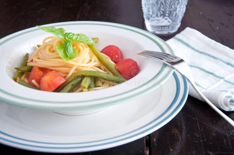 Espaguetes com os feijões verdes e os tomates de cereja frescos imagem de stock