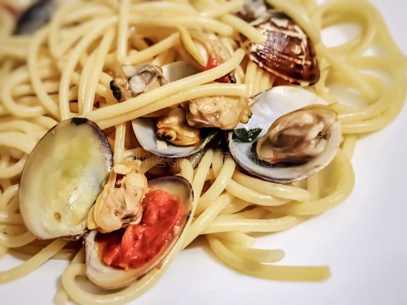 Espaguetes com os moluscos minúsculos do bebê no shell imagens de stock