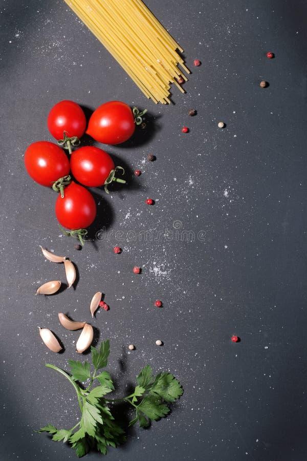 Espaguetes com tomates, alho e salsa de cereja no fundo preto fotografia de stock royalty free