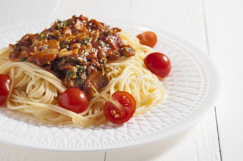 Espaguetes cozinhados com molho de cogumelo e tomates de cereja em uma placa branca Fundo de madeira branco fotografia de stock