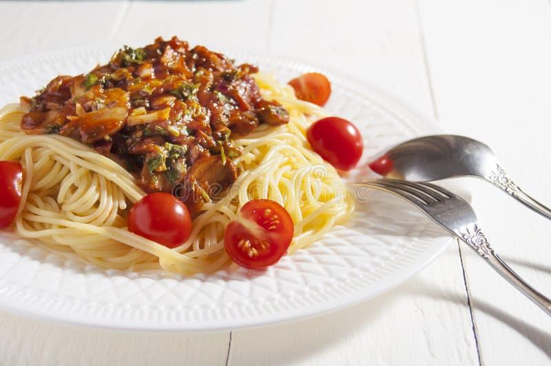 Espaguetes cozinhados com molho de cogumelo e tomates de cereja Forquilha, colher e placa branca Fundo de madeira branco imagem de stock royalty free