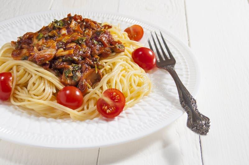 Espaguetes cozinhados com molho de cogumelo e tomates de cereja Forquilha e placa branca Fundo de madeira branco imagens de stock