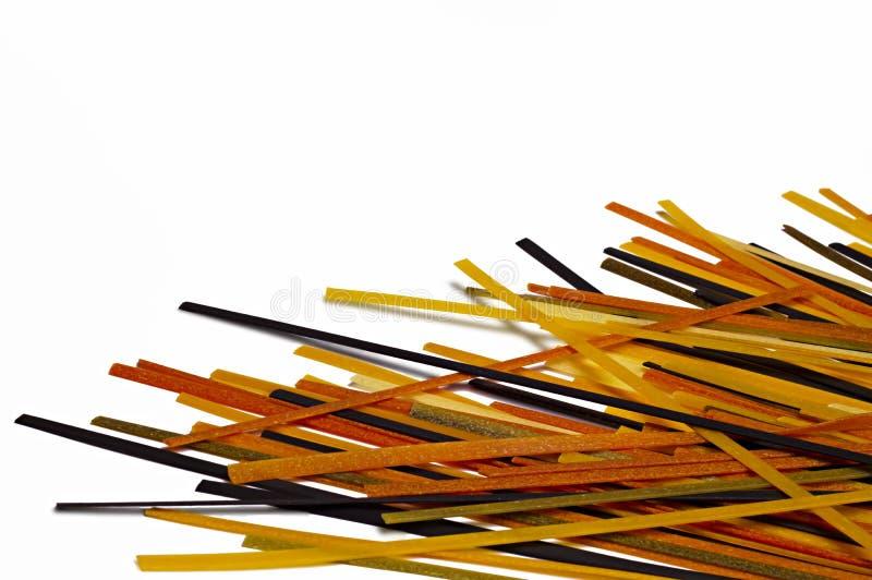 Espaguetes crus coloridos dispersados isolados no branco Backgrou do alimento imagem de stock