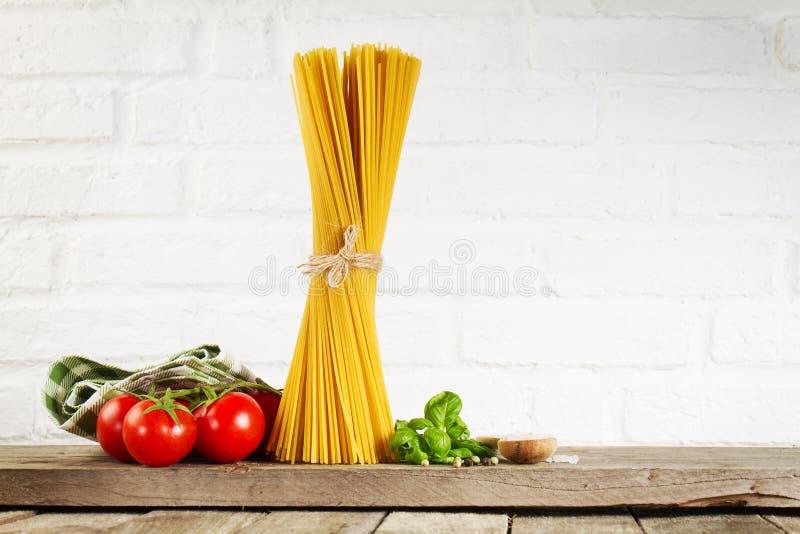 Espaguetes crus do alimento italiano colorido fresco saboroso na mesa de cozinha imagem de stock