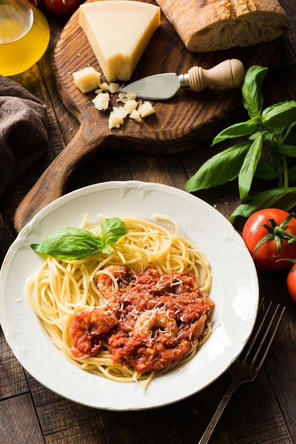 Espaguetes da massa com molho e camarões de tomate na madeira rústica imagens de stock