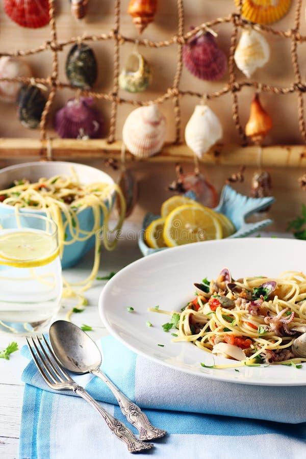 Espaguetes do marisco em uma tabela branca com fundo da concha do mar fotos de stock royalty free