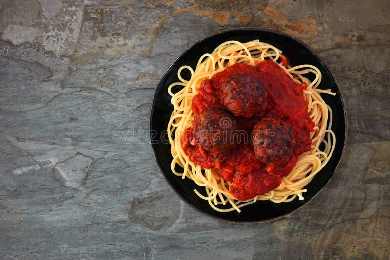 Espaguetes e almôndegas com molho de tomate, vista superior sobre a pedra escura fotos de stock royalty free