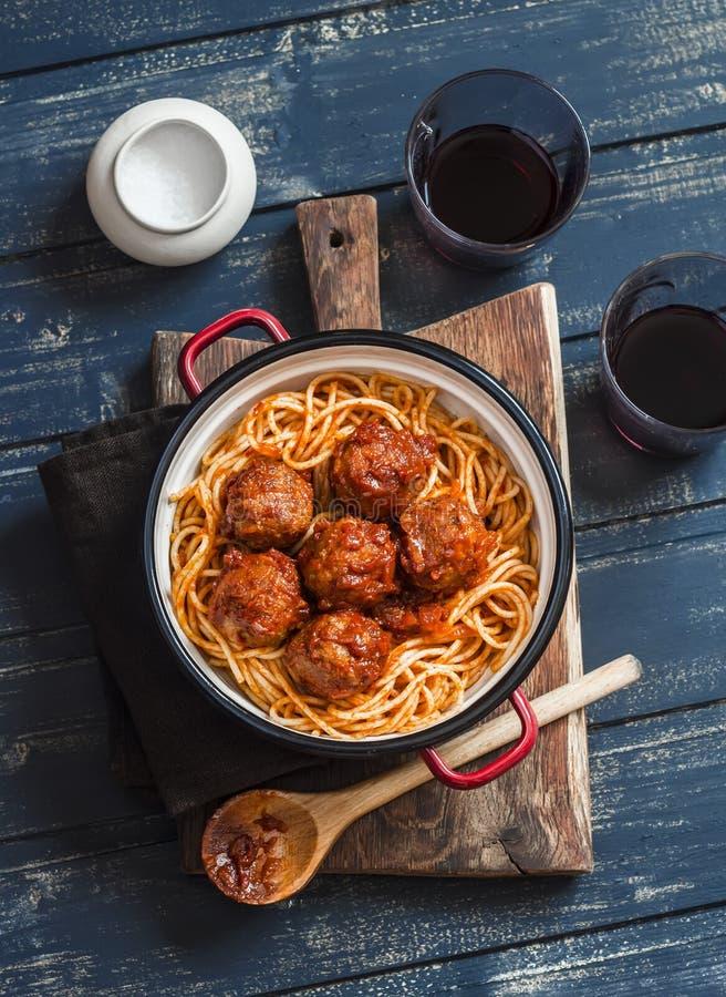 Espaguetes e almôndegas no molho de tomate e nos dois vidros com vinho tinto na placa rústica de madeira imagem de stock