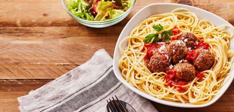 Espaguetes e almôndegas servidos com salada lateral fotografia de stock