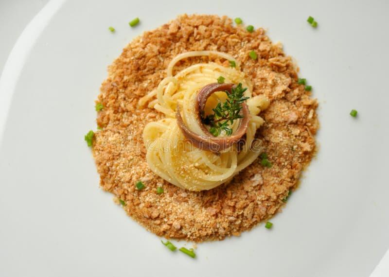 Espaguetes italianos com migalhas e anchova de pão foto de stock