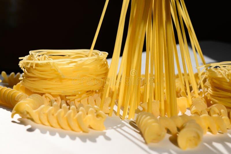 Download Espaguetes, Massa Do Ninho, Fusilli Na Luz Do Sol Na Tabela Branca Imagem de Stock - Imagem de saudável, ingrediente: 80100073