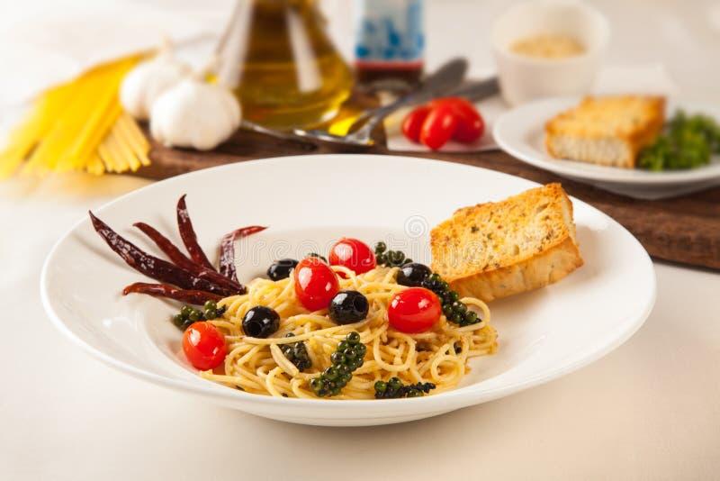 Espaguetes, pimento fresco e azeitonas pretas Com pão de alho fotografia de stock royalty free