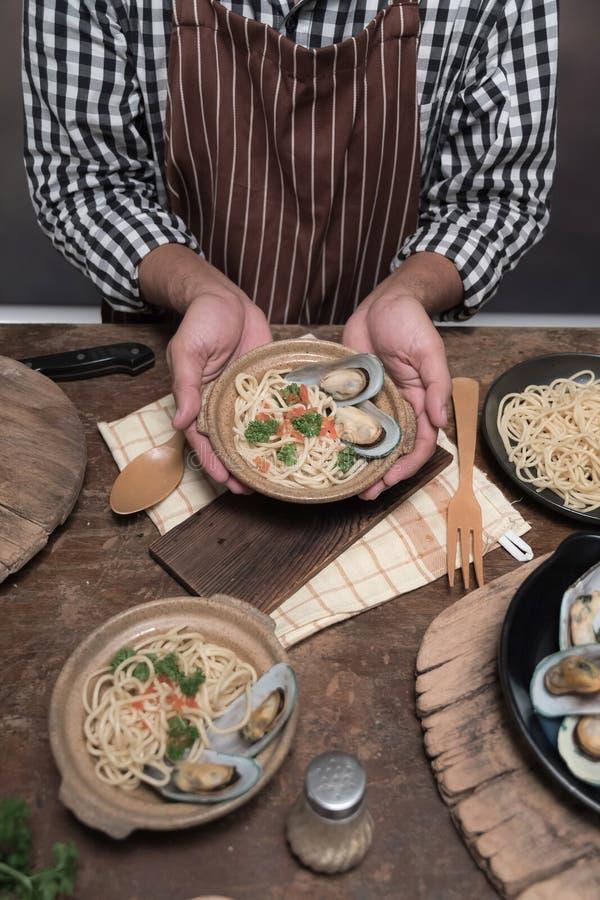 Espaguetes prepairing do cozinheiro farpado considerável do cheef em uma cozinha foto de stock royalty free