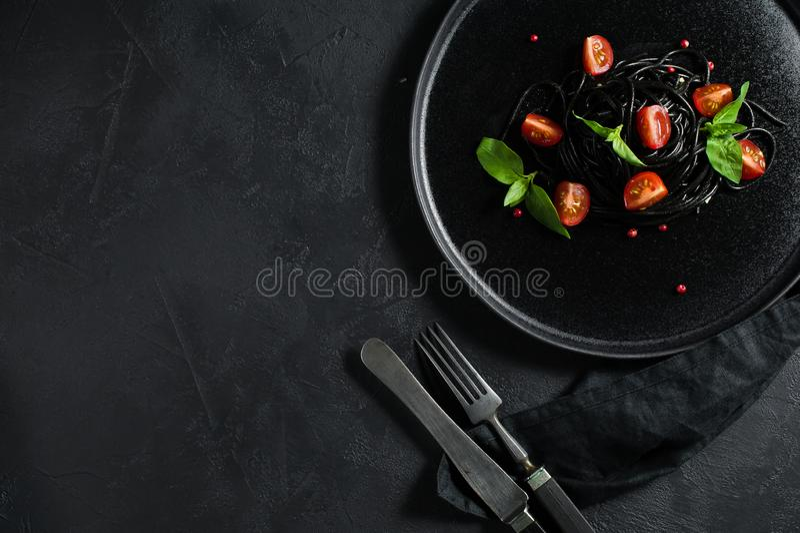 Espaguetes pretos com os tomates da manjeric?o e de cereja, massa do vegetariano Fundo preto, vista superior, espa?o para o texto fotografia de stock royalty free
