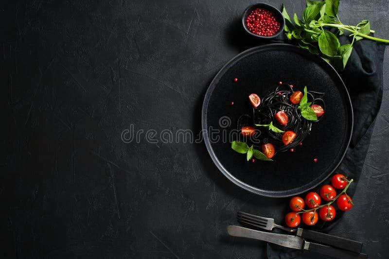 Espaguetes pretos com os tomates da manjeric?o e de cereja, massa do vegetariano Fundo preto, vista superior, espa?o para o texto imagem de stock royalty free