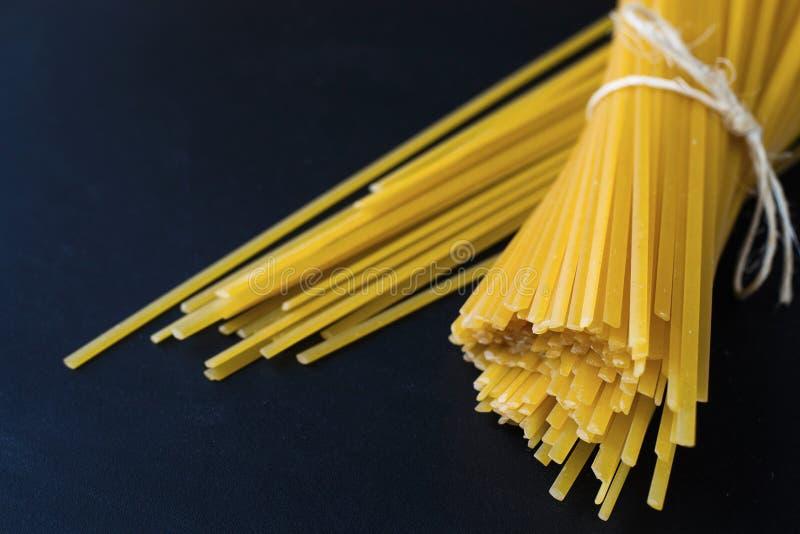 Espaguetes secos da massa no fundo preto imagens de stock royalty free