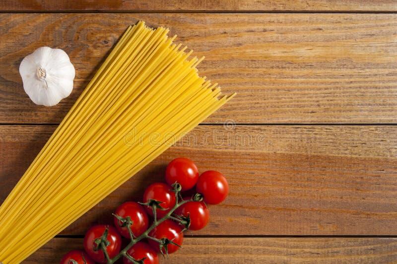 Espaguetes, tomates de cereja e cabeça do alho em uma tabela de madeira marrom Tomates à direita dos espaguetes, alho à esquerda  imagem de stock royalty free