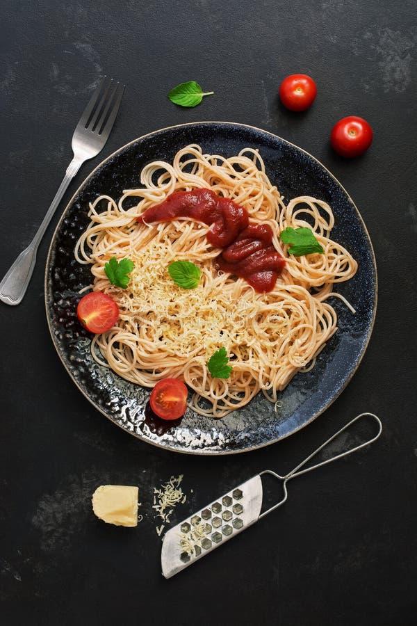Espaguetes tradicionais da massa com molho, queijo parmesão e verdes de tomate em um fundo de pedra preto Vista superior, configu fotos de stock royalty free