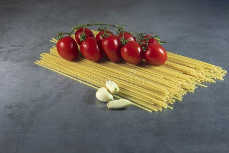 Espagueti con los tomates y el ajo de cereza fotos de archivo libres de regalías