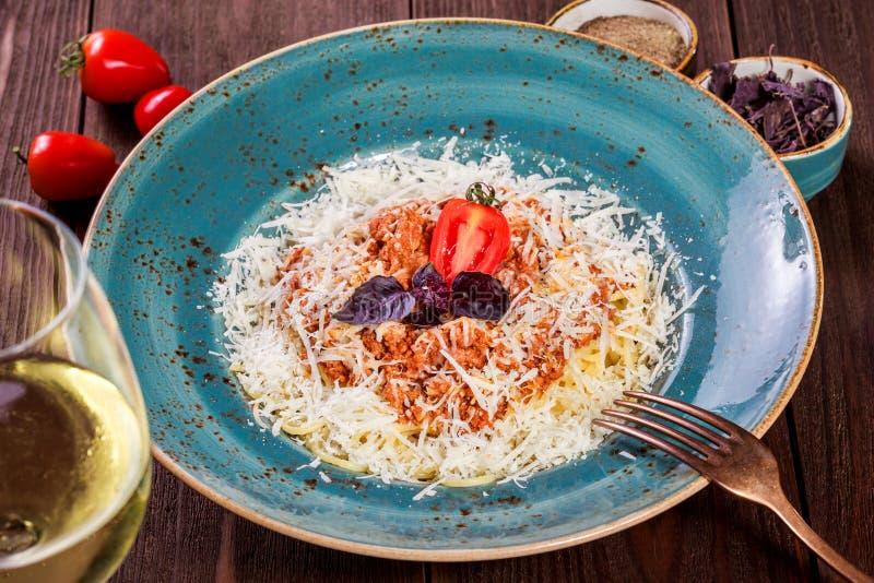 Espaguetis boloñés con carne de vaca picadita, la salsa de tomate adornada con el queso parmesano y la albahaca en la placa foto de archivo libre de regalías